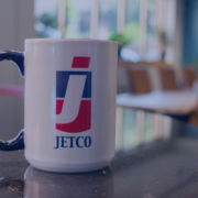 JetCo Logo on coffee mug with office in the background