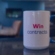 JetCo Federal coffee mug that says win contracts with the office in the background